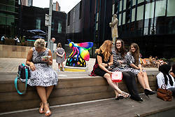 """© Licensed to London News Pictures . 26/07/2018. Manchester , UK . Bee in the City sculpture outside HOME . """"Bee-bop-a-raver"""" by Caroline Daly . Over 100 bee sculptures , decorated and painted by different artists , have been placed across Manchester City Centre . The worker bee is Manchester's symbol , reflecting the City's heritage as the home of the industrial revolution . Photo credit : Joel Goodman/LNP"""