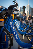 A row of blue bicycles that are part of the bike share program in Melbourne, Australia. In the background two people read about how to use the program. (August 2017)