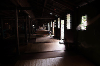 Old woman weaving a basket in a shaft of light in the communal area of the Murat Longhouse, Skrang River, Sarawak, Borneo, Malaysia.