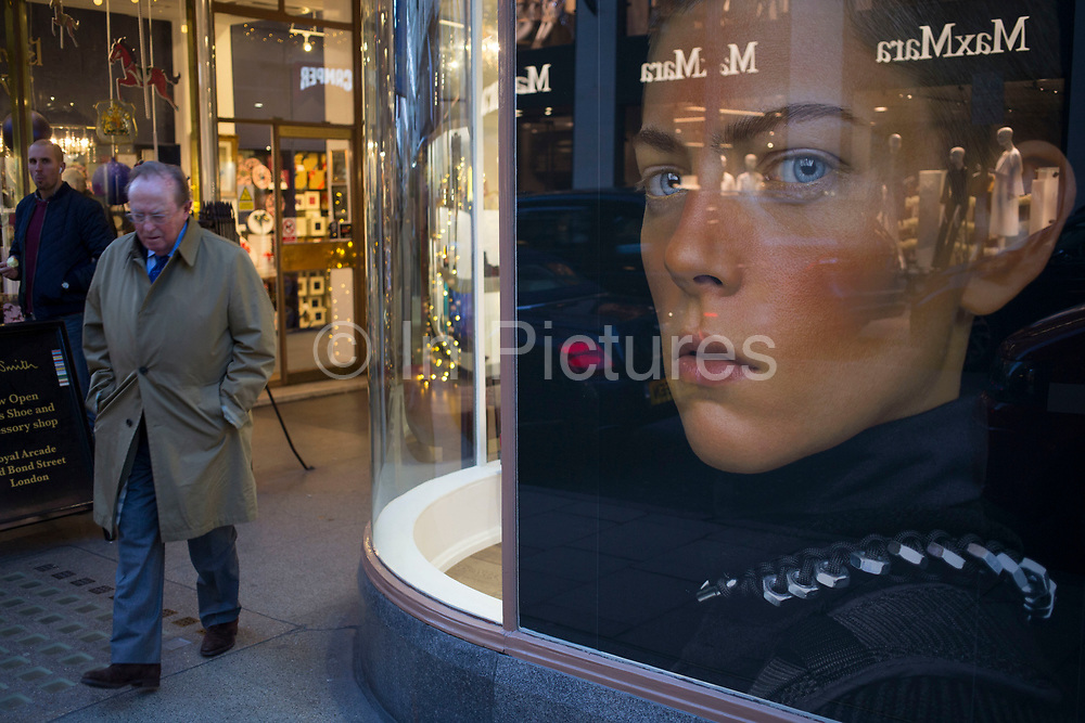 Photograph of a man's head with stark staring eyes makes an interesting street scene as people interact. New Bond Street, London, UK. A weird visual juxtaposition is created as people integrate with the large scale window display.