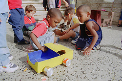 Children playing with a toy lorry made from recycled cardboard and tins at a nursery school in Havana; Cuba,