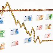 Nederland Barendrecht 29 maart 2009 20090329 Foto: David Rozing ..dalende grafiek in euromunten, zakken, dalen, minder waard worden, index, in het rood gaan, waarde vermindering, dip, recession, dalende, indexgrafiek, grafieken, in de min gaan, mineur, pessimisme, teruglopend, teruglopende resultaten, tegenvallend, tegenvallenden, waardevermindering, beursindex, beurs, bel, bubble, valuta, betaalmiddel, kosten,betaalmiddelen,recessie, kredietcrisis, economie, negatief, negatieve, zwakke econonomie, zakken, zakkende, verslechteren, minder waard worden, aandelen, kapitaalafname, afnemen, afname, .money , euro stockbeeld, stockfoto, stock, studio opname, illustratie, .bankbiljetten, valuta, betaalmiddel, kosten,papiergeld,biljet,biljetten,bankbiljet,bankbiljetten,eurobiljet,eurobiljetten, .Foto: David Rozing