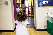 A toddler watches a prison officer through one of the locked barred doors during a family visit in HMP Brixton, South London on the 26th of July 2016, London United Kingdom. The Prisoner Advice & Care Trust (PACT) organise special family days that help the men inside the prison connect with and support their partners and children on the outside. (photo by Andy Aitchison)