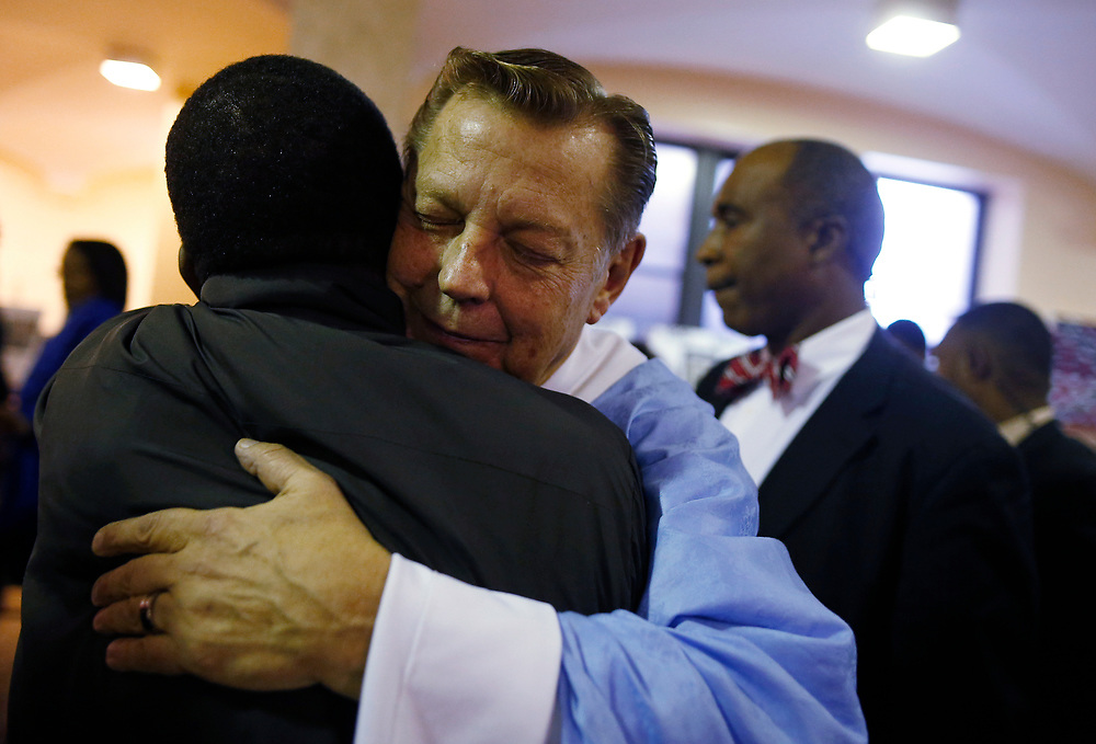 Father Michael Pfleger (C) hugs a parishioner after a Sunday Service at Saint Sabina Church in Chicago, Illinois, U.S., December 4, 2016.    REUTERS/Jim Young