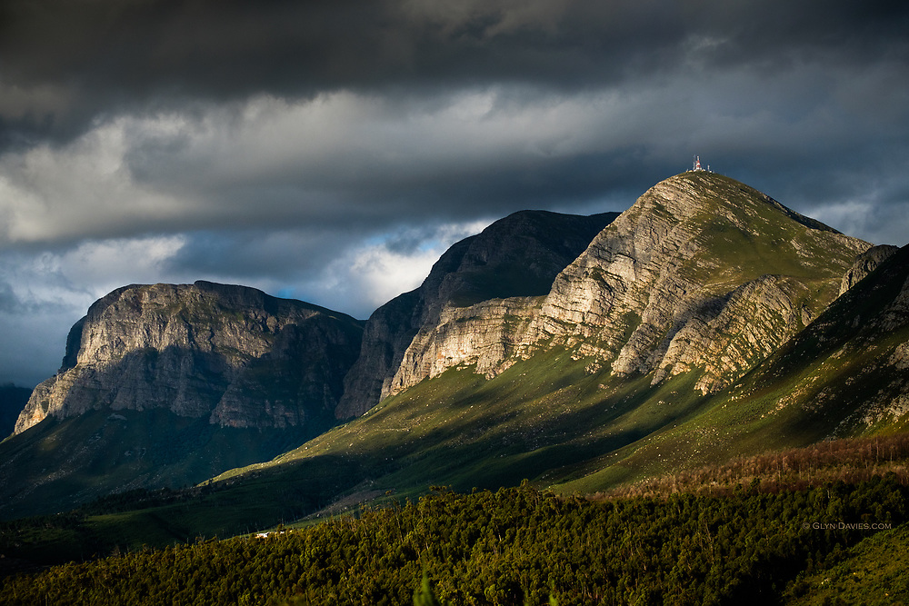 Evening light spilled under the clouds to illuminate the incredible and imposing Hottentots-Holland mountain range (part of the Cape Fold Belt) East of Cape Town. These mountains reach 1590 m / 5200 ft at their highest point.