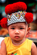 THAILAND, NORTH, GOLDEN TRIANGLE Chiang Mai, display of traditional Akha hilltribe hat on portrait of child