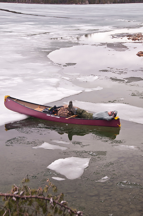 A canoeist relaxes among ice floes during an early spring trip to Lady Evelyn-Smoothwater Provincial Park in Ontario Canada.