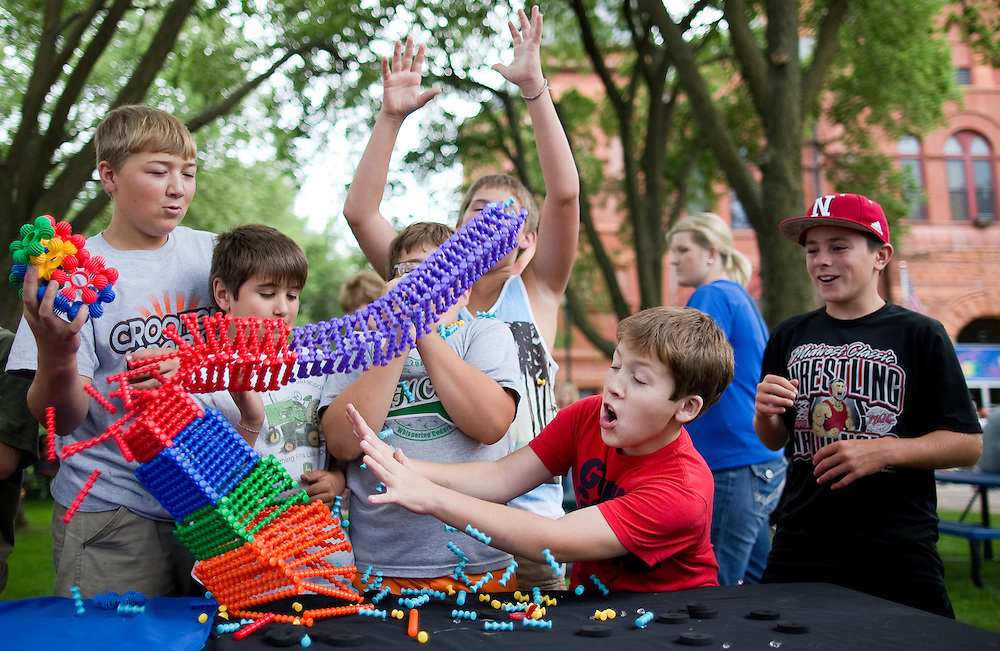 From left, Brad McDonald, 13, Jeremy Oswalkd 11, Kyle Sullican, 11, Seth Wonch, 12, Kaden Skorniak, 12, and Trevor Kluck, 11, react as the tower they created quickly collapses during Family Night of A'ron'n Days Thursday evening in Courthouse Square in Aurora. (Independent/Matt Dixon)