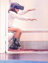 Girl sitting on toilet bowl and wearing virtual reality glasses