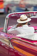 Close up of man in hat driving car, Havana, Cuba