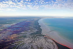 Clouds refelcted in wet season floodwater in the hinterland of Roebuck Bay.  A plume of sedminent empties into Roebuck Bay.