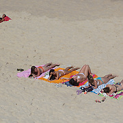 Sunbathers on Ipanema beach, Rio de Janeiro, Brazil. 6th July 2010. Photo Tim Clayton..The beaches of Rio de Janeiro, provide the ultimate playground for locals and tourists alike. Beach activity is in abundance as beach volley ball, football and a hybrid of the two, foot volley, are played day and night along the length and breadth of Rio's beaches. .Volleyball nets and football posts stretch along the cities coastline and are a hive of activity particularly at it's most famous beaches Copacabana and Ipanema. .The warm waters of the Atlantic Ocean provide the ideal conditions for a variety of water sports. Walkways along the edge of the beaches along with exercise stations and cycleways encourage sporting activity, even an outdoor gym is available at the Parque Do Arpoador overlooking the ocean. .On Sunday's the main roads along the beaches of Copacabana, Leblon and Ipanema are closed to traffic bringing out thousands of people of all ages to walk, run, jog, ride, skateboard and cycle more than 10 km of beachside roadway. .This sports mad city is about to become a worldwide sporting focus as they play host to the world's biggest sporting events with Brazil hosting the next Fifa World Cup in 2014 and Rio de Janeiro hosting the Olympic Games in 2016..