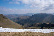 Stunning mountain range of Lake District National Park from western side of Helvellyn Mountain, Lake District, Cumbria, UK. It is a bright, sunny day, but there is snow on the ground along the mountain side. Helvellyn is the third-highest point in England and is located in the beautiful Lake District National Park and part of the Eastern Fells.