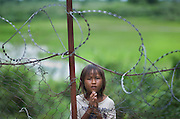 A little girl begs for money outside the barbed wire fence at the Killing Fields museum in Cambodia. The museum was a former school in Phnom Pehn used as a prison where Cambodians were interrogated, tortured, and murdered by the Khmer Rouge. The Khmer Rouge ruled Cambodia from 1975 to 1979.  While in power the Khmer Rouge murdered, worked to death, or killed by starvation close to 1.7 million Cambodians, or more than one-fifth of the country?s population...