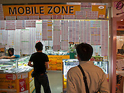 09 OCTOBER 2009 -- BANGKOK, THAILAND: Shopping for a phone number in the Mahboonkrong (MBK)  shopping center in Bangkok, Thailand. MBK is an immense six story shopping mall with department stores, restaurants, a hotel and thousands of small shops and stalls. It is more like a vast indoor market than a shopping mall. Thais are firm believers in numerology and frequently try to buy phone numbers they think will bring them the best luck.     PHOTO BY JACK KURTZ