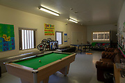 The Common Room social area with games in the Healthcare Wing of HMP Pentonville, London, UK. HM Prison Pentonville is an English Category B men's prison, operated by Her Majesty's Prison Service. The room contains sofas, television, pool and table-tennis tables. There are colourful posters on the wall. (Photo by Andy Aitchison)