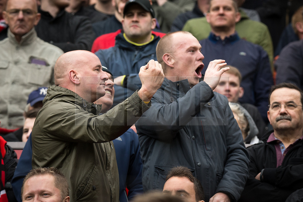 © Licensed to London News Pictures . 17/05/2015 .  Old Trafford , Manchester , UK . Manchester United fans gesture at Arsenal fans during the match . Manchester Utd vs Arsenal at Old Trafford Football Stadium , Manchester . Photo credit : Joel Goodman/LNP