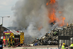 © Licensed to London News Pictures. 21/06/2014; Trowbridge, WIltshire, UK.  A large fire broke out at Shanleys Metal Recycling Centre in Trowbridge this morning and was still burning with flames leaping up several hours later, and with Wiltshire Fire & Rescue Service in attendance.  Several roads in the town were closed and the smoke could be seen for miles.<br /> Photo credit: Simon Chapman/LNP
