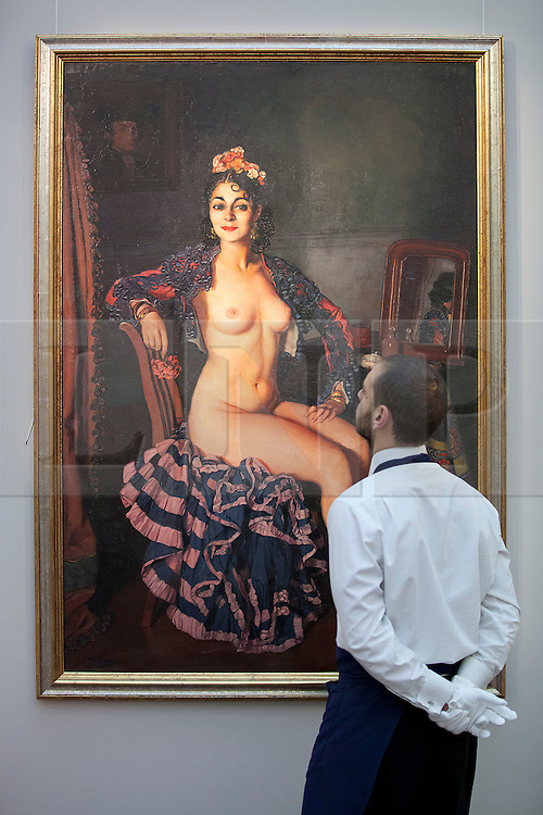 © Licensed to London News Pictures. 16/11/2012. London, UK. A Sotheby's employee looks at 'La Oterito' (1936) (est. GB£500,000-700,000), a painting by Spanish artist Ignacio Zuloaga, at a press call taking place at the London based auction house's New Bond Street premises today (16/11/12).  The sale, featuring works by 19th century European painters, is set to take place on the 20th of November. Photo credit: Matt Cetti-Roberts/LNP