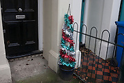 A discarded tinsel Christmas tree, sitting on the porch outside a house near Elephant & Castle, on 4th January, London borough of Southwark, England.