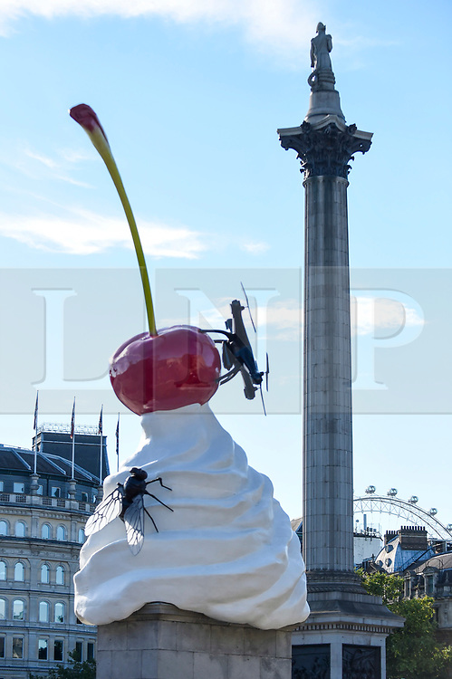 © Licensed to London News Pictures. 30/07/2020. LONDON, UK.  Artist Heather Phillipson's 'THE END', is unveiled to the public as the new Fourth Plinth artwork in Trafalgar Square.  THE END shows a giant swirl of replica whipped cream topped with a cherry, a fly and a drone.  Its drone transmits a live feed of the square which can be watched on a dedicated website.  The installation, originally planned for 26 March 2020 but postponed due to the coronavirus pandemic, will remain on display for the next year two years.  Photo credit: Stephen Chung/LNP