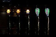 Beers on tap at a bar, including the Belgian abbey beer Grimbergen and the Polish beer Okocim.