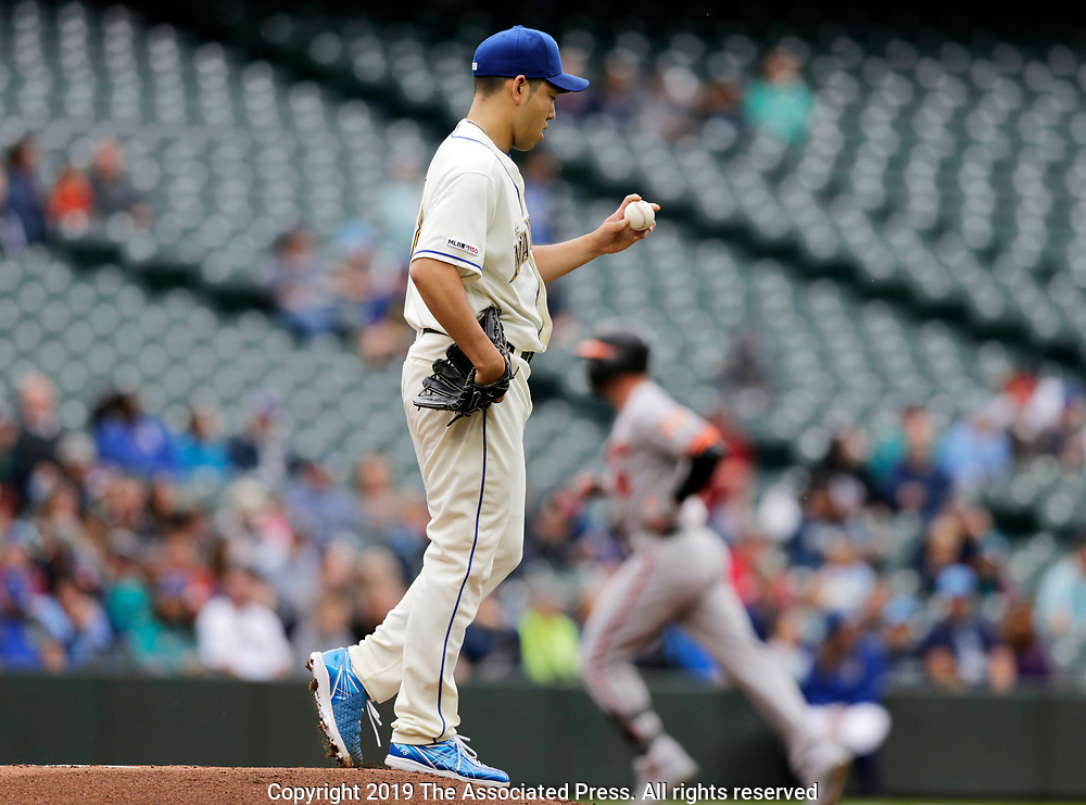 Seattle Mariners starting pitcher Yusei Kikuchi looks at a new baseball as Baltimore Orioles' Trey Mancini rounds the bases after hitting a solo home run during the first inning of a baseball game, Sunday, June 23, 2019, in Seattle. (AP Photo/John Froschauer)