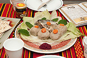 Gefilte fish with carrot. A traditional Askenazi Jewish festive dish of poached fish patties made from a mixture of ground deboned carp, traditionally eaten on Passover Seder
