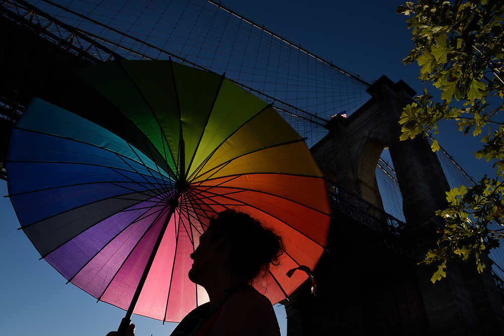 A large umbrella shades a woman from the late afternoon sun as the Brooklyn Bridge looms overhead on the last day of Photoville along Brooklyn Bridge Plaza in New York City, NY. Produced by United Photo Industries, the free annual festival is a pop-up village built from re-purposed shipping containers that are filled with galleries and talks.