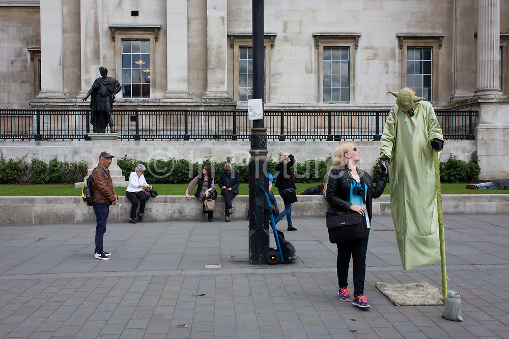 Street busker dressed as Star Wars character Yoda with tourists in Trafalgar Suare. A woman tourist holds Yoda's hand and other pedestrians in the background experience the madness of characters dressed as fantasy characters in this central London loaction. In the background is the statue of James II as a Roman emperor, wearing Roman armour and a laurel wreath – traditionally awarded to a victorious Roman commander.