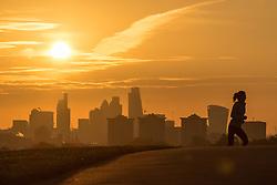 Primrose Hill, London, October 28th 2016. A woman runs up Primrose Hill as the sun rises over London's skyscrapers.