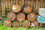 Rusty old oil barrels stacked in a boat yard in Norfolk, England, UK