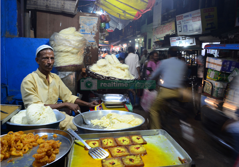 June 15, 2018 - Allahabad, India - An indian muslim vendor waits for customers in his sweet shop , on the eve of Muslim's holy festival Eid Ul Fitr , in the old market of Allahabad on June 15 , 2018 ..Eid al-Fitr (feast of breaking the fast ) is an important religious festival celebrated by muslims worldwide that marks the end of Ramadan,the islamic holy month of fasting. (Photo by Ritesh Shukla  (Credit Image: © Ritesh Shukla/NurPhoto via ZUMA Press)