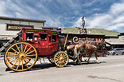 The Castagno Outfitters tourists stagecoach drives past the Million Dollar Cowboy Bar around the the Town Square in Jackson Hole, Wyoming.