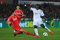 Swansea City's Bafetimbi Gomis is tackled by Liverpool's Adam Lallana<br /> <br /> Photographer Kevin Barnes/CameraSport<br /> <br /> Football - Barclays Premiership - Swansea City v Liverpool - Monday 16th March - The Liberty Stadium - Swansea<br /> <br /> © CameraSport - 43 Linden Ave. Countesthorpe. Leicester. England. LE8 5PG - Tel: +44 (0) 116 277 4147 - admin@camerasport.com - www.camerasport.com