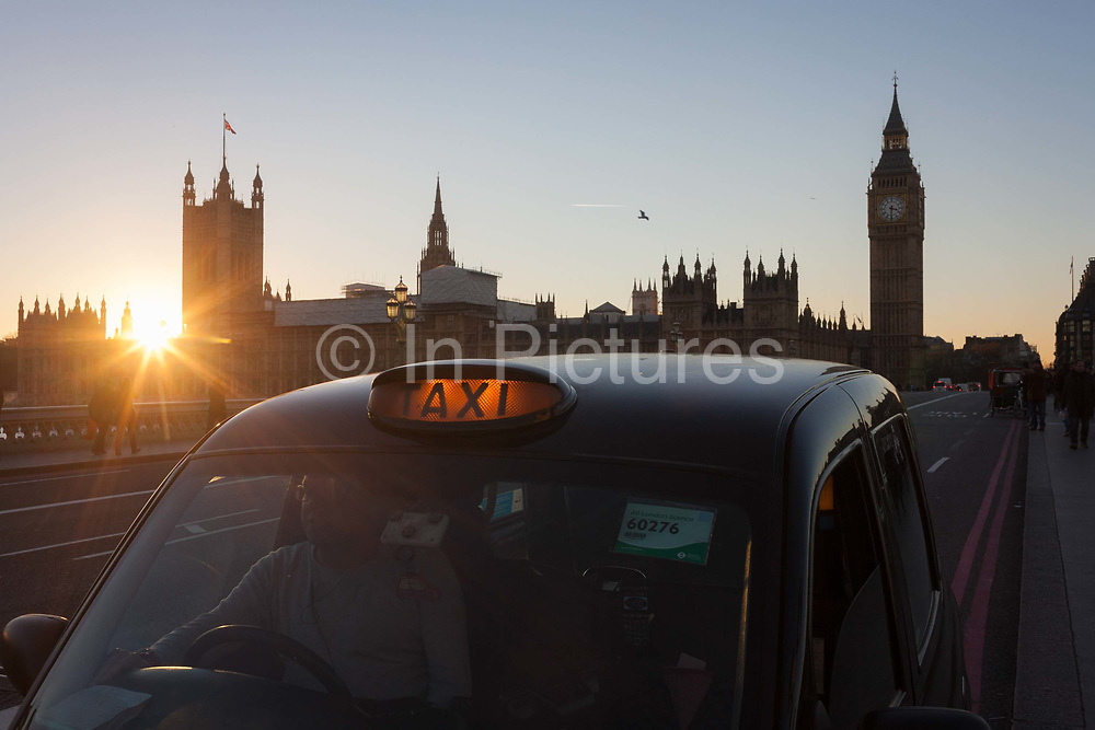 With a setting sun, Big Ben and the Houses of Parliament in the distance, a black London taxi is stopped on Westminster Bridge awaiting a fare, on 29th November 2016, in London, England. Across the brdge, the sun sets behind the Houses of Parliament, currently undergoing major renovation works.