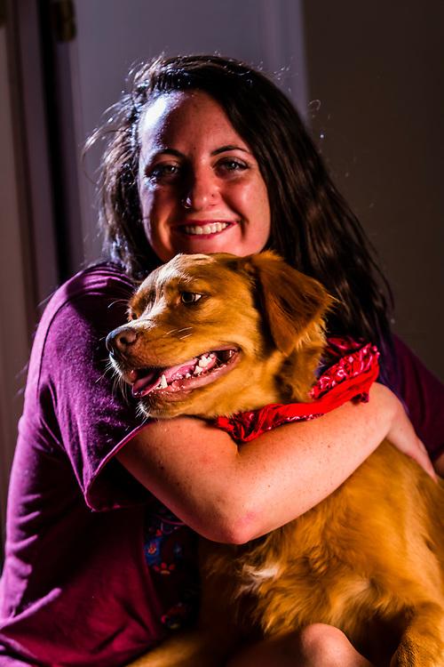 A young woman with her dog, an Australian Shepherd/Golden retriever mix, Littleton, Colorado USA.
