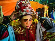 08 DECEMBER 2016 - BANGKOK, THAILAND: A cast member adjusts the head gear of her costume before going on stage at a Chinese opera (also called ngiew in Thailand) performance at Pek Leng Keng Shrine in the Khlong Toei neighborhood of Bangkok. Public performances of music and celebration were banned during the first 30 days of the mourning period for Bhumibol Adulyadej, the Late King of Thailand. Now, nearly two months after the revered monarch's death, Bangkok street life is returning to normal and Chinese temples and shrines are once again scheduling operas.      PHOTO BY JACK KURTZ