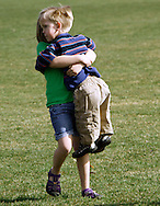 First grader Adam Kotzian (R) is lifted by a classmate during physical education at Eagleview Elementary school in Thornton, Colorado March 31, 2010.  Adam and his parents are achondroplasia dwarfs but his sister Avery is not.   REUTERS/Rick Wilking (UNITED STATES)