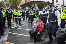 London, UK. 13 October, 2019. Police officers arrest a disabled climate activist from Extinction Rebellion using Section 14 of the Public Order Act 1986 during a protest outside New Scotland Yard against tactics employed by police officers which impinge on the right to protest of disabled activists, including the confiscation of wheelchairs, wheelchair ramps, accessible toilets and tents.