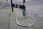Locked up bent bicycle wheel. London, UK. One of the hazards of cycling in London is the level of bike crime. Despite being locked up, Londoners know they always have some risk that their cycle may be stolen.