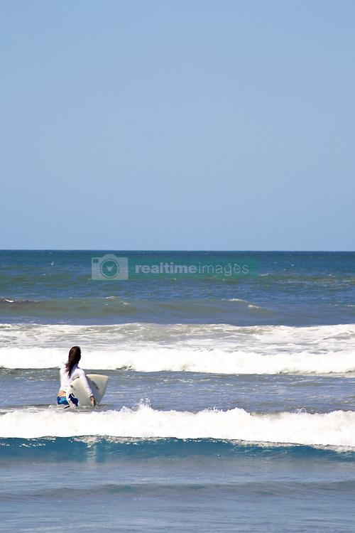 July 21, 2019 - Woman Taking Surfboard Into Sea (Credit Image: © Caley Tse/Design Pics via ZUMA Wire)