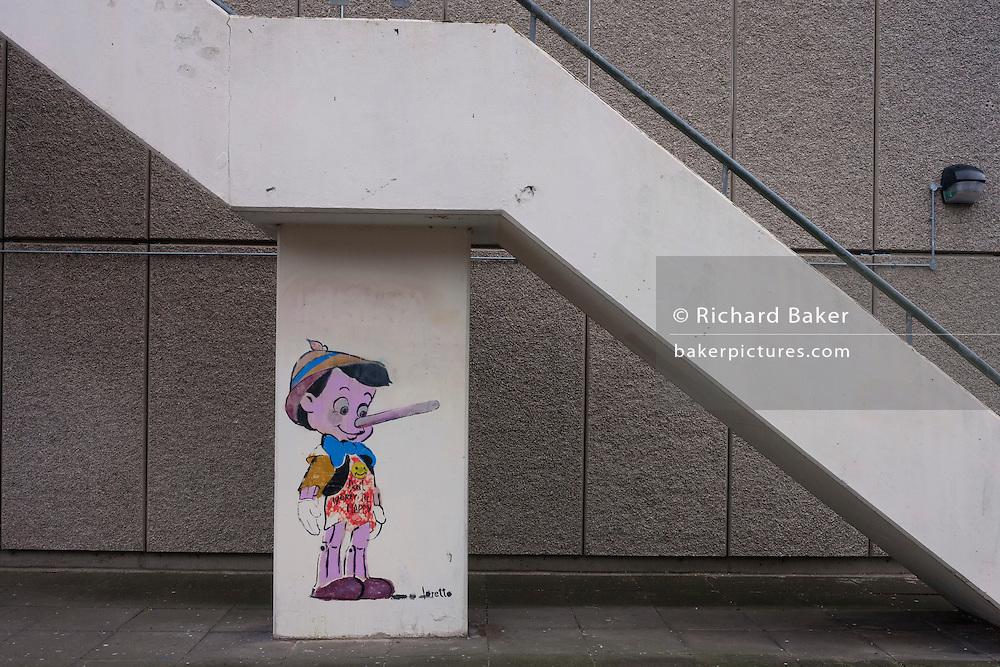 The Disney cartoon character Pinoccio, beneath concrete stairs on the Aylesbury Estate, on 4th January, London borough of Southwark, England.