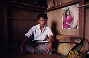 LOGGING, MALAYSIA. Sarawak, Borneo, South East Asia. Logging camp. Migrant worker with gun, in cabin with bedroll and posters. Tropical rainforest and one of the world's richest, oldest eco-systems, flora and fauna, under threat from development, logging and deforestation. Home to indigenous Dayak native tribal peoples, farming by slash and burn cultivation, fishing and hunting wild boar. Home to the Penan, traditional nomadic hunter-gatherers, of whom only one thousand survive, eating roots, and hunting wild animals with blowpipes. Animists, Christians, they still practice traditional medicine from herbs and plants. Native people have mounted protests and blockades against logging concessions, many have been arrested and imprisoned.