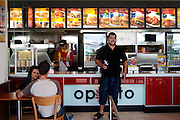 A man stands at the counter of Oporto, a fast-food establishment at Bondi Beach, Sydney, Australia. Other, bigger international fast food restaurants line the beach road. (Supporting image from the project Hungry Planet: What the World Eats.)