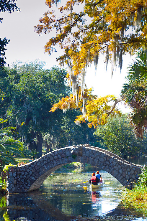 Canoeing on a preserved bayou under the Langles Bridge, built in 1902, at City Park in New Orleans. City Park is one of the United States oldest urban parks and holds the world's largest collection of mature live oaks.
