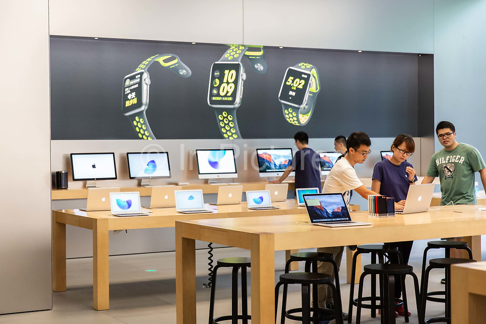 Customers look at mac laptops on offer at the Apple Store inside the IAPM shopping mall in Shanghai, China, on Friday, Sept. 16, 2016. iPhone sales are slowing in Chinas Apples second largest market, as local upstarts such as Huawei and Xiaomi are eating into the companys high end market.