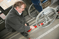 Bus driver securing wheelchair of wheelchair user on transport resource for people with physical and sensory impairment.