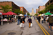 15 MAY 2021 - DES MOINES, IOWA: People walk through the Des Moines Farmers Market with the historic Polk County Courthouse in the background. The Des Moines Farmers Market is the largest weekly Farmers Market in Iowa. The market was largely cancelled in 2020 because of COVID-19 pandemic, but reopened in a limited way in 2021. In order to comply with Coronavirus safety guidelines, traffic is one way past the stands and people are required to wear face masks. Traditionally about 25,000 people attended the Saturday morning market, and about 40,000 people attended market on the opening day, the first Saturday in May. This year there will be about 115 vendors, 75% the normal number of vendors. As the CDC rolls back Coronavirus guidelines, the market is expanding. The market will expand Memorial Day weekend to include prepared food stands and children's activities.        PHOTO BY JACK KURTZ