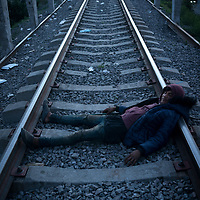 An exhausted migrant rests on the rails of the freight train network known as La Bestia. Apizaco, Tlaxcala, Mexico.